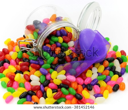 Jelly Beans in Glass Jar with large Purple Plastic Easter Egg and Purple Ribbon - stock photo