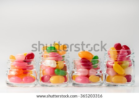 Jelly beans in small glass jars on white background - stock photo