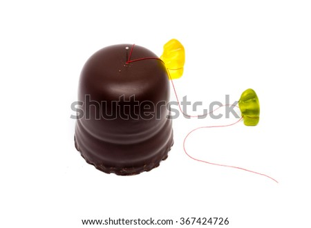 Jelly bears climbing the chocolate mountain - chocolate covered marshmallows .german schokokuss with shadow on white - stock photo