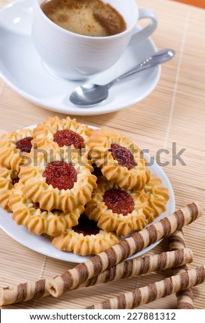 Jelly cookies pile and black coffee in cup, little teaspoon lying on saucer. Aromatic traditional beverage with delicious and decorated cookies with red jelly, vertical orientation - stock photo