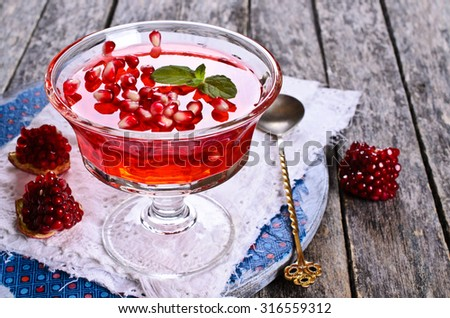 Jelly red with pomegranate and mint in a glass container - stock photo