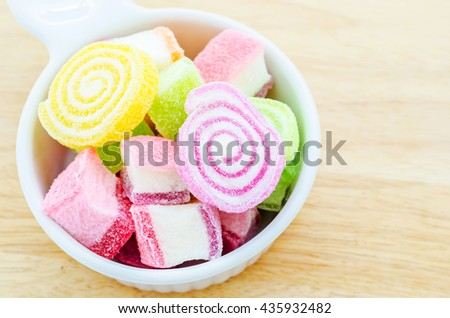 Jelly sweet, flavor fruit, candy dessert colorful in white cup on wooden background. - stock photo