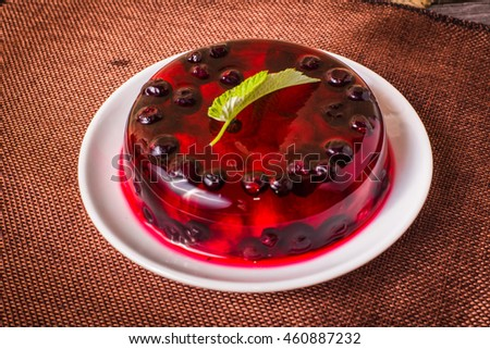 jelly with raspberries and cranberries on a wood table