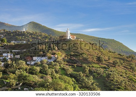 Jemaa Bouzafar, a small 15th century mosque on a hill above the town of Chefchaouen in the Rif mountains of North West Morocco at the end of sunny day - stock photo