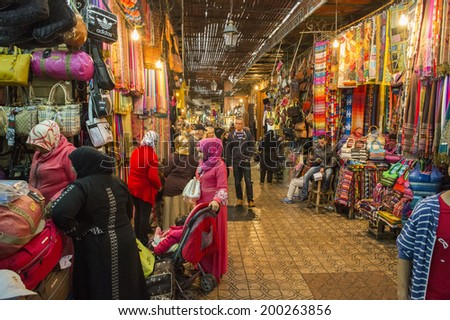 JEMMA DAR FNA, THE MAIN BAZAAR, MARRAKECH, MOROCCO, MAY 11, 2014. People walking on a corridor surrounded by booths and stalls in Jemma Dar Fna, Marrakech, Morocco, on May 11th, 2014.  - stock photo