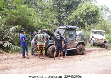 Jerantut, Malaysia - 20 October 2015 : Group off road 4x4 helping each other when vehicle breakedown in thick forest in rainforest Malaysia