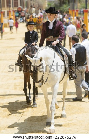 JEREZ DE LA FRONTERA, SPAIN-MAY 17: Amazon mounted on horse and dressed in typical Andalusian costume, on fair ride on May 17, 2014 in Jerez de la frontera. - stock photo
