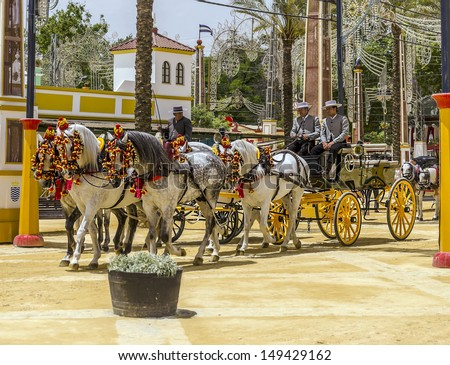 JEREZ DE LA FRONTERA, SPAIN-MAY 10:People in carriage horses walking in the royal house of the fair on the horse fair the day May 10, 2013 in Jerez de la Frontera,  - stock photo