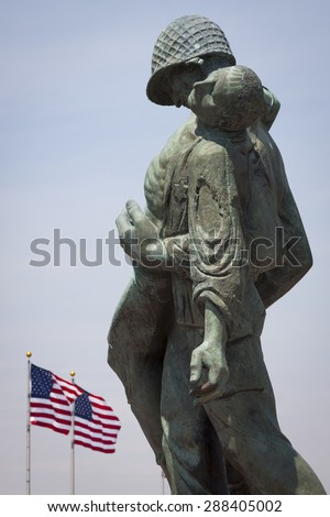 JERSEY CITY, NJ - MAY 26 2015: The Liberation Monument, a Holocaust memorial depicting a US soldier carrying a Nazi death camp survivor, with American Flags in the US Flag Plaza in Liberty State Park. - stock photo