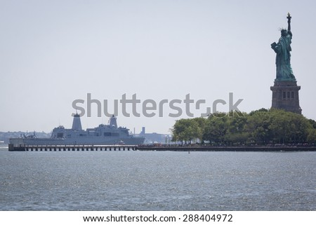 JERSEY CITY, NJ - MAY 26 2015: USS San Antonio (LPD 17) passes the Statue of Liberty on the Upper New York Bay after departing Pier 92 at the end of Fleet Week NY 2015. - stock photo