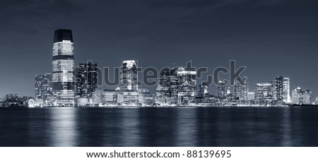 Jersey City skyline with skyscrapers at night black and white over Hudson River viewed from New York City Manhattan downtown. - stock photo