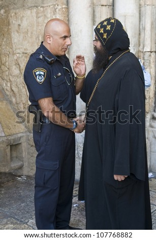 JERUSALEM - APRIL 13: Coptic priest meet with Israeli police officer at the church of the Holy Sepulcher in Jerusalem Israel during Good Friday on April 13 2012 - stock photo