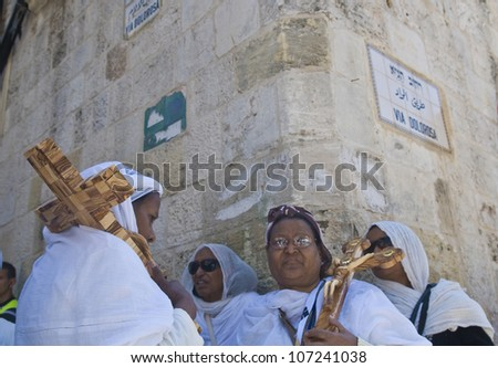 JERUSALEM - APRIL 13 : Ethiopian Christian pilgrims carry across along the Via Dolorosa in Jerusalem on April 13 2012 commemorating the path Jesus carried his cross on the day of his crucifixion