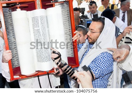 JERUSALEM, ISRAEL - APRIL 26: Jewish reading pray from Torah, ancient scrolls at the western wall on a jewish holiday Israel's 64th Independence Day on April 26, 2012 in Jerusalem, Israel - stock photo