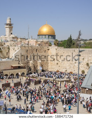 JERUSALEM, ISRAEL - APRIL 17, 2014: The Western Wall crowded with Passover prayers, and the Dome of the Rock in the background, in the old city of Jerusalem, Israel