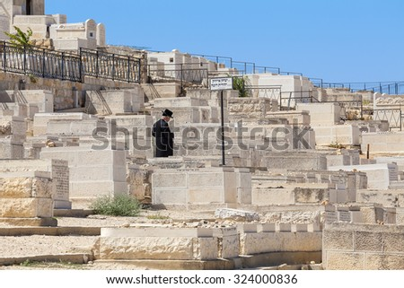 JERUSALEM, ISRAEL - JULY 13, 2014: Man prays on Jewish cemetery on Mount of Olives - most ancient and important cemetery where burials started 3,000 years ago with about 70,000 tombs. (Focus on man). - stock photo