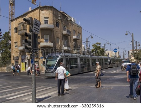 Jerusalem,Israel - July 31,2015: Pedestrians and Light Rail on busy streets of downtown Jerusalem during Friday preparation for the Evevning of Shabbat.Jerusalem, July 31,2015