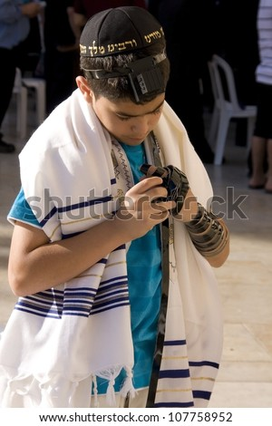 JERUSALEM , ISRAEL - MAY 31 : unidentified  Jewish boy prays in The western wall on May 31 2012, The Western wall is important Jewish religious site located in the Old City of Jerusalem , Israel - stock photo