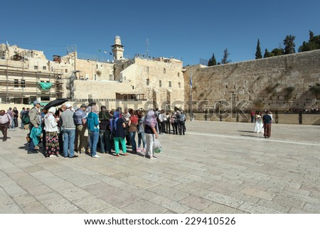 Jerusalem, Israel - November 9, 2014 : Group of Tourists at Jerusalem's wailing wall compound with blue sky and  the wailing wall in the background