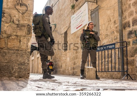 Jerusalem, Israel - November 3, 2015: Israeli soldiers - man and woman - guarding one of the mai street in old city - stock photo