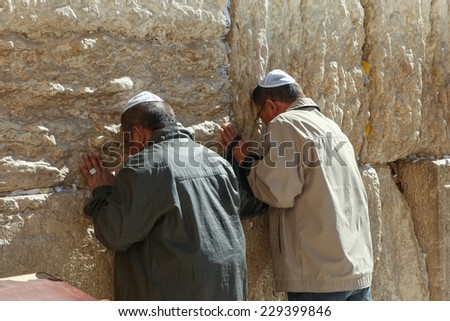 Jerusalem, Israel - November 9, 2014 : Two men  pray at the western wall. The western wall is an exposed section of ancient wall situated on the western flank of the Temple Mount.