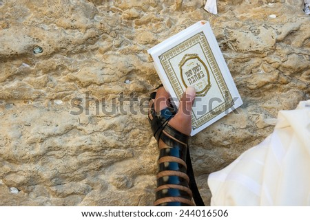 JERUSALEM, ISRAEL - OCT 06, 2014: A jewish man with the torah in his hand and tefillin around his arm is praying against the western wall in the old city of Jerusalem - stock photo