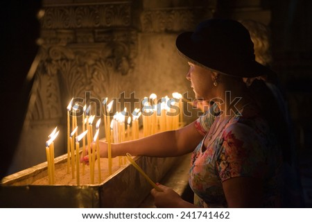 JERUSALEM, ISRAEL - OCT 06, 2014: A woman is burning a candle close at the place where Jesus Christ was crucified in the Church of the Holy Sepulchre in Jerusalem. - stock photo