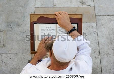 JERUSALEM, ISRAEL - OCT 08, 2014: An jewish man is reading in the torah near the wailing wall in Jerusalem - stock photo