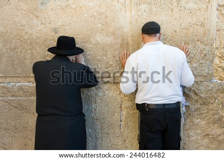 JERUSALEM, ISRAEL - OCT 06, 2014: Two jewish man are praying against the western wall in the old city of Jerusalem - stock photo