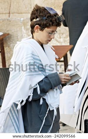 JERUSALEM, ISRAEL - OCTOBER 31, 2014:  An unidentified Jewish boy worshiping at the Western Wall. - stock photo
