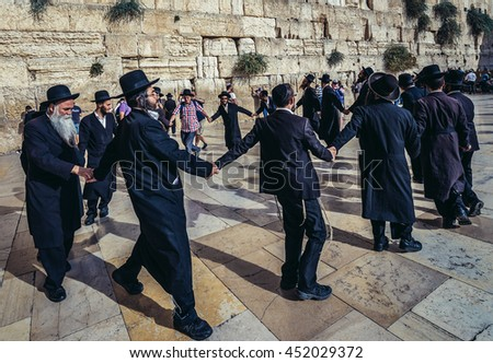 Jerusalem, Israel - October 22, 2015. Group of Orthodox Jews dances next to ancient limestone wall known as Wailing Wall in the Old City of Jerusalem