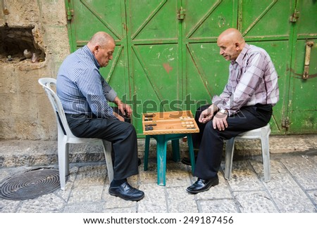 JERUSALEM, ISRAEL - OCTOBER 07, 2014: Two elderly men are playing backgammon in one of the small streets in the old city of Jerusalem - stock photo