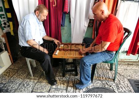JERUSALEM - JULY 30: old Arab men playing backgammon on July 30 2009 in Jerusalem, Israel.It's one of the oldest board games for two players in the world. - stock photo