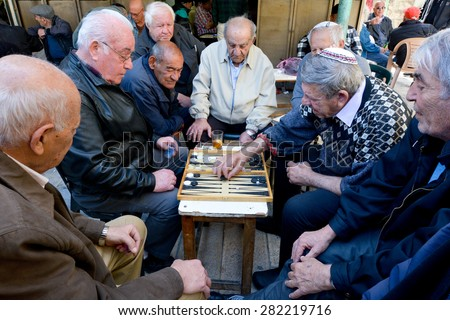 JERUSALEM - MAR 25 2015:Elderly men play backgammon in Mahane Yehuda Market in Jerusalem, Israel. Backgammon is among the oldest known board games, and many variants are played throughout the world. - stock photo