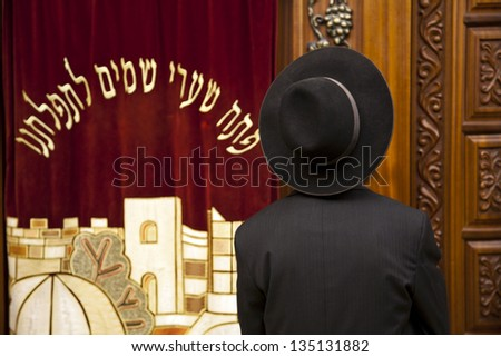 "JERUSALEM - MAY 21: Jewish man standing in front of a cabinet that contains holy Torah scrolls. The Hebrew text translates to ""Open heaven's gates to our prayer"" on May 21 2010 in Jerusalem, Israel - stock photo"