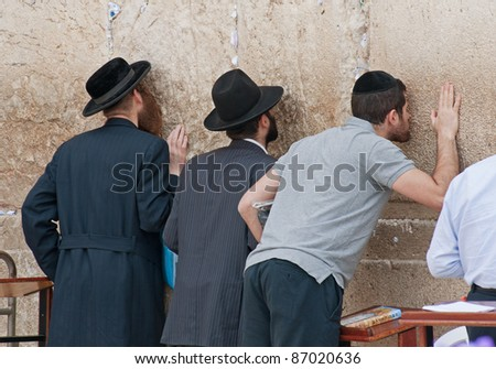 JERUSALEM - MAY 10 : The wailing Wall main religious symbol of Israel. Three jews praying at the wailing wall in the threshold of the holiday Lag ba-Omer on May 10, 2009 in Jerusalem. - stock photo