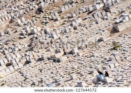 JERUSALEM - NOV 12:Jewish couple visit a grave on Mount of Olives on November 12 2008 in Jerusalem ,Israel.  The Jewish cemetery on Mt olives is over 3,000 years and holds approximately 150,000 graves - stock photo