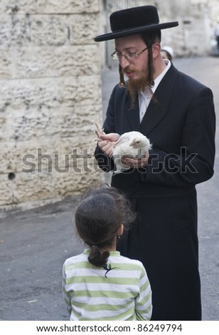 "JERUSALEM - OCT 06 : An ultra Orthodox Jewish man waves a chicken over his daughter's head during the ""Kaparot"" ceremony held in Jerusalem Israel in October 06 2011 - stock photo"