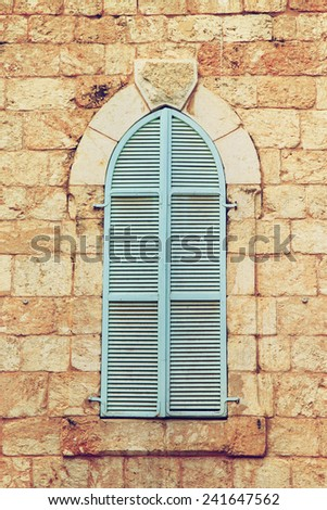 Jerusalem's ancient building's wall with blue aqua window shutters. retro filtered image - stock photo