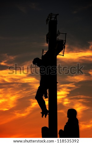 Jesus christ crucifixion in Prague. 17th Century Crucifixion statue on Charles Bridge in Czech Republic capital. Image is taken against the light in the sunset. - stock photo
