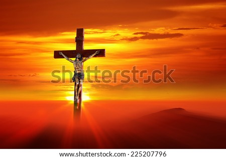 Jesus christ on cross against a background of the Sun set sky