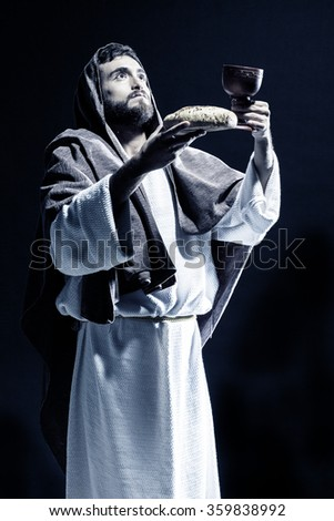 Jesus Christ praying to God consecration the bread and grapes in the dark black night. Black and white - stock photo