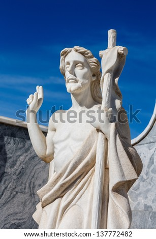 Jesus Christ stone in the cemetery on a grave and cross in hand - stock photo