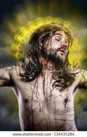 Jesus Christ with a halo of golden light on the cross - stock photo