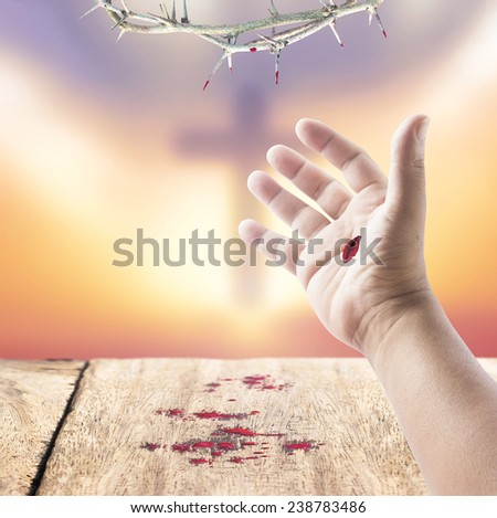 Jesus hand and drops of blood on wooden floor over blurred the cross on a sunset. Christmas background, Forgiveness, Mercy, Humble, Reconcile, Adoration, Glorify, Redeemer, Redemption, Gospel concept. - stock photo