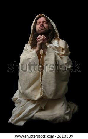 Jesus in prayer on his knees on dark background - stock photo
