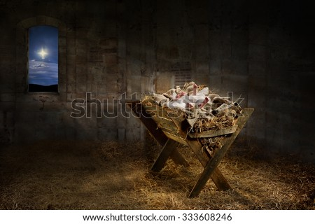 Jesus resting on a manger while light from the star filters into the room - stock photo