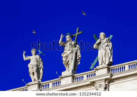 Jesus sculptures and sacred, standing on a roof of the Papal Basilica of Saint Peter, Vatican, against the blue sky and two flying birds - stock photo