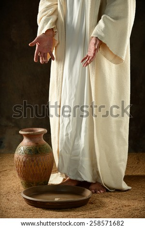 Jesus standing before a jar of water inside a precarious building - stock photo