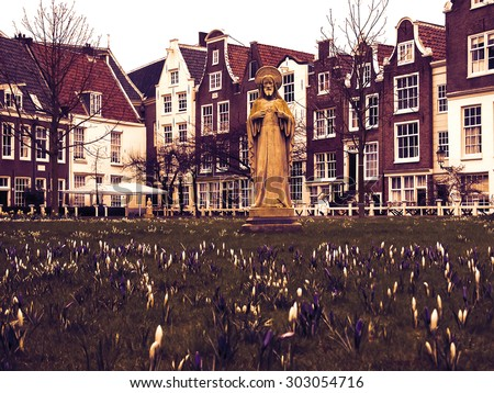 Jesus statue surrounded by violet and white crocus flowers and historic houses in Begijnhof courtyard. (Amsterdam, Netherlands) Toned photo. - stock photo